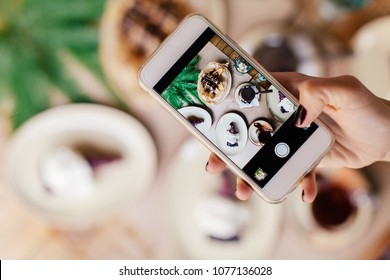 Woman taking photo of dishes at the cafe. Breakfast, social media, blogger's life, outdoors.