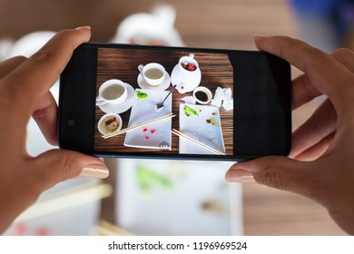 Woman taking photo empty dirty plate of sushi on table in cafe