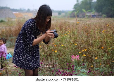 the woman taking photo of flowers