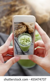 Woman taking a photo of green tea frappe by smartphone