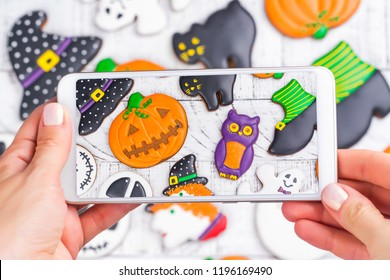 Woman taking photo of halloween gingerbread cookies on mobile phone. Trendy instagram photo shot. Copy space. Top view, flat lay style