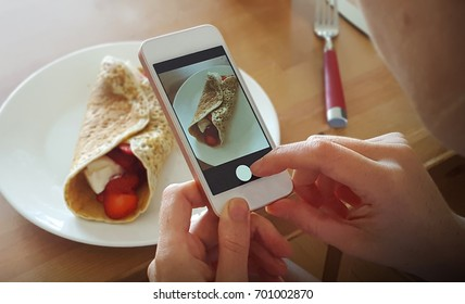 Woman taking a photo of her breakfast