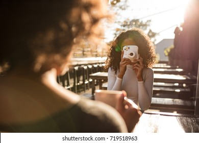 Woman taking photo of her friend using an instant digital camera. Woman holding a coffee cup being photographed by her friend outdoors.