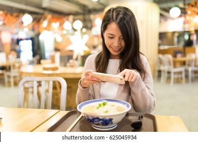 Woman taking photo in her ramen in restaurant