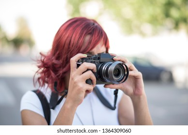 woman taking photo with mirroless camera in outdoors image