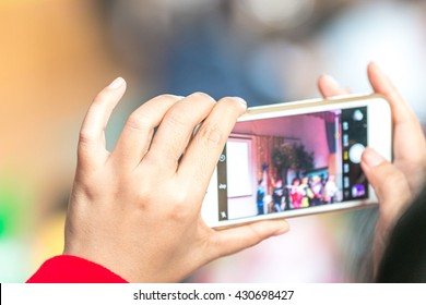 woman taking photo with mobile phone