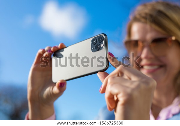 Woman taking photo with modern triple-lens camera phone