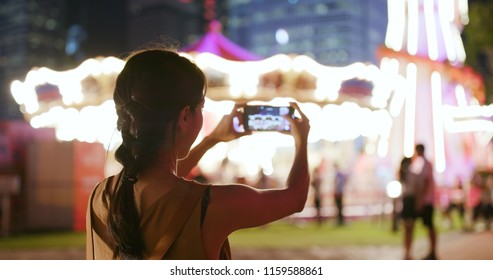 Woman taking photo on carousel in the city at night