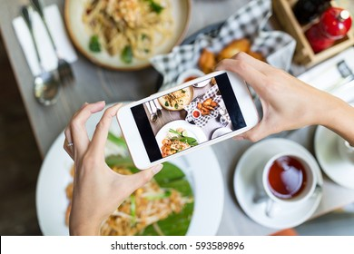 Woman taking photo on cellphone on dish