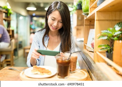 Woman taking photo on food in cafe