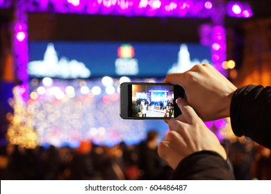 Woman taking photo on smartphone at open air concert