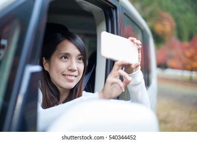 Woman taking photo outside a car