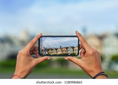 Woman taking a photo of San Francisco with her Smart phone