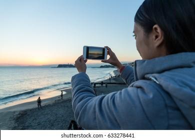 Woman taking photo in Shonan of Japan