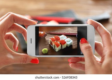 Woman taking photo of tasty sushi set