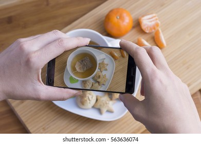 Woman taking photo of tea breakfast and tangerine with mobile phone