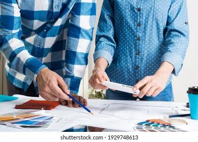 Frau fotografiert technische Zeichnung mit Smartphone. Designer, die mit Farbmustern arbeiten und Baupläne am Arbeitsplatz erstellen. Inneneinrichtung, architektonische Dekoration und Renovierung.