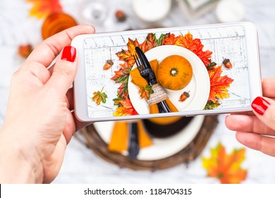 Woman taking photo of Thanksgiving day table setting. Trendy instagram photo shot. Copy space. Top view, flat lay style