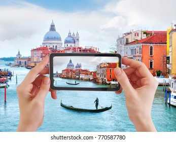 Woman taking photo of Traditional gondola in Venice, basilica Santa Maria della Salute