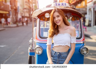 woman taking a photo with an Tuk-Tuk vehicle or Thai traditional taxi in Bangkok Thailand background.