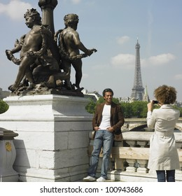 Woman taking photograph of man next to statue in Paris