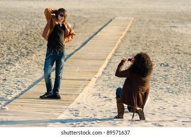 Woman taking photographs of a teenager on the beach
