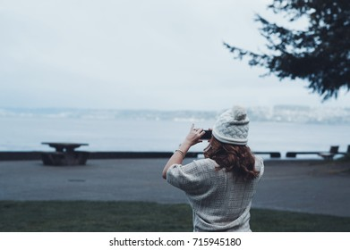 Woman Taking Photos with Phone in Cold Weather