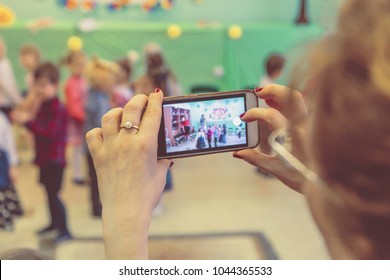 woman taking a picture of children on the phone in kindergarten