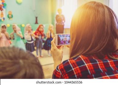 Frau, die am Telefon im Kindergarten ein Kinderbild macht