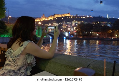 Woman taking picture of a city weekend in outdoor restaurant.