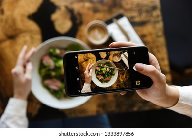Woman taking a picture of her lunch while sitting at the cafe indoors