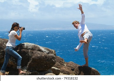 A woman is taking a picture of a man, who appears to be falling off a cliff overlooking the ocean.