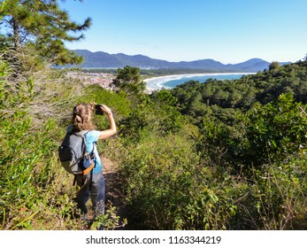Woman taking a picture of Mocambique beach viewed from Boa vista hiking path - Florianopolis, Brazil