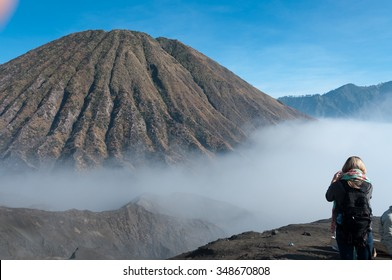 Woman taking a picture of the Mountain with fog and mist at volcano Bromo