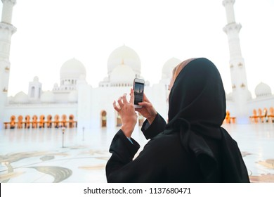 Woman taking picture of Sheikh Zayed Grand Mosque by mobile phone
