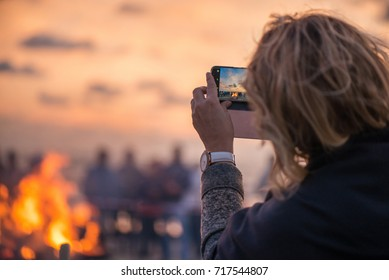 Woman is taking picture of sunset with smart phone. Romantic bonfire night at seaside. People gathering together to celebrate Night of ancient lights. Large burning campfire with soft glowing flame.