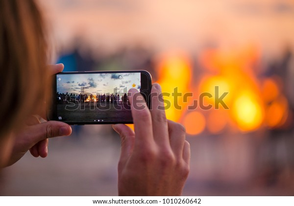 Una mujer toma fotos de la puesta del sol con un smartphone. Noche romántica de fuego en la costa. Gente reuniéndose para celebrar la Noche de las luces antiguas. Gran fogata ardiendo con una llama suave y brillante.