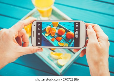 Woman taking picture of vintage tray with fruits on her smartphone. Top view
