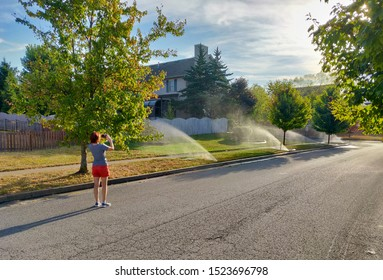 Woman taking picture of water sprinklers on street of american town on hot sunny day.