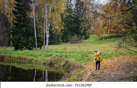 A woman taking pictures at autumn forest in Saint Petersburg, Russia.