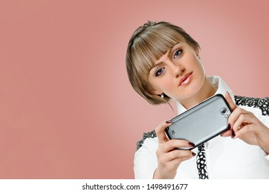 Woman taking pictures with black cellphone. Cheerful brunette using phone camera on background salmon shade red