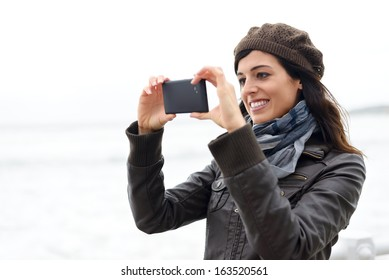 Woman taking pictures with black cellphone. Cheerful brunette using phone camera.