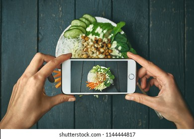 woman taking pictures buddha bowl with vegan food, fried chickpeas, rice noodles with wegetables on blue wooden table using phone. Woman Food photographer with hands visible photographing for the