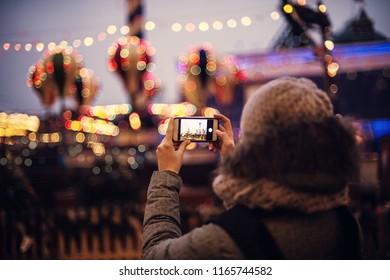 Woman Taking Pictures of European Christmas Market Scene on Smartphone. Girl Enjoying Winter Holiday Season, visiting Outdoors Christmas Market.