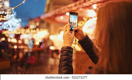 Woman Taking Pictures of European Christmas Market Scene on Smartphone. 4K. Girl Enjoying Winter Holiday Season, visiting Outdoors Christmas Market, Making photos on cell phone. Travel Europe