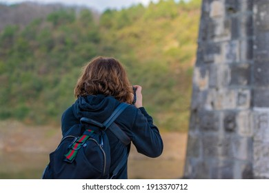 woman taking pictures in nature. Portrait of woman pointing back. natural background. photographer girl.