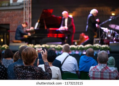 Woman is taking pictures or recording video of jazz concert. Male musicians on stage singing, playing piano, saxaphone, drums, cello. Crowded venue. Audience enjoying romantic and relaxing evening