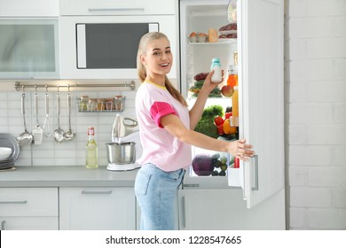 Woman taking products out of refrigerator in kitchen