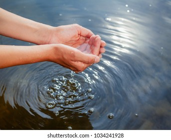 Woman taking raw unfiltered water from a natural source by cupped hands