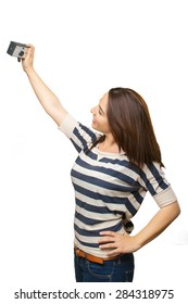 Woman taking a self portrait with a retro camera. Over white background